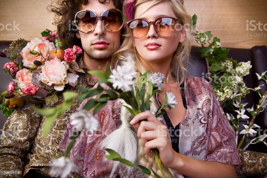 Young Hippie Man and Woman Holding Flowers stock photo