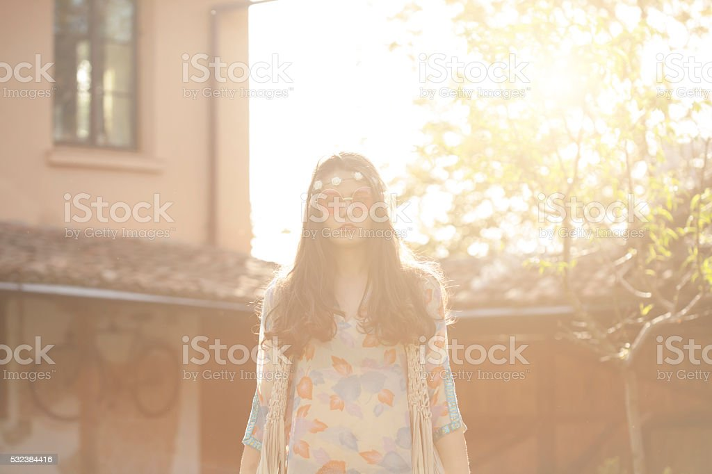 Young hippie woman standing at back yard stock photo