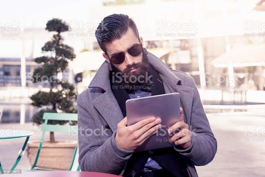 young hipster businessman consults his laptop stock photo