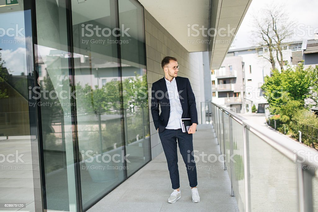 Young hipster businessman in glasses near office outdoor stock photo
