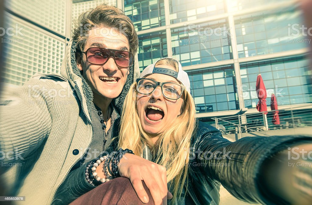Young hipster couple in love taking selfie in urban area stock photo