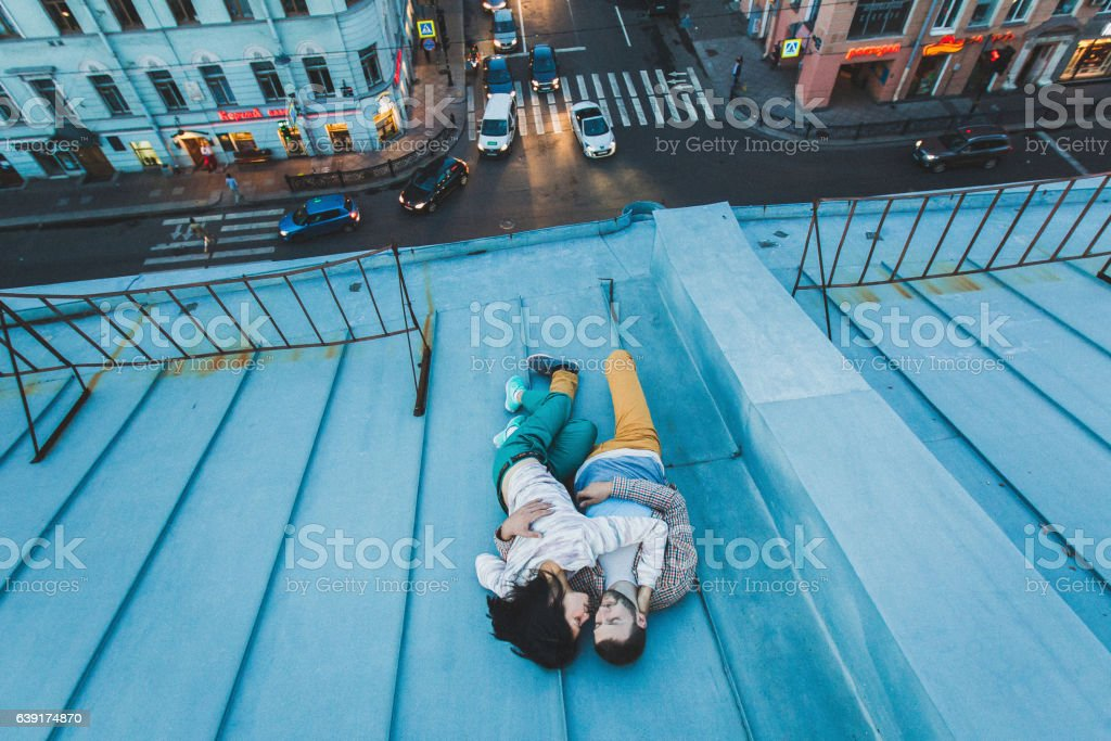 Young hipster couple lying on roof and kissing. Beautiful view stock photo