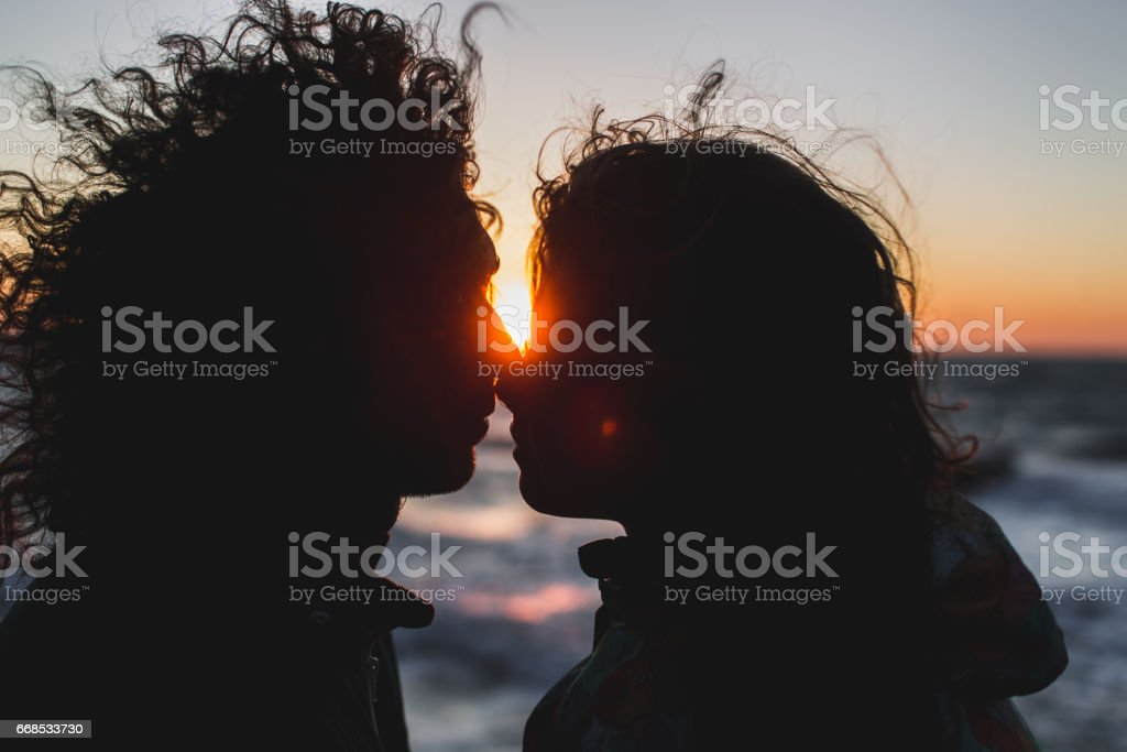 Young hipster couple with long curly hair kissing at sunset. Sensual close-up portrait stock photo
