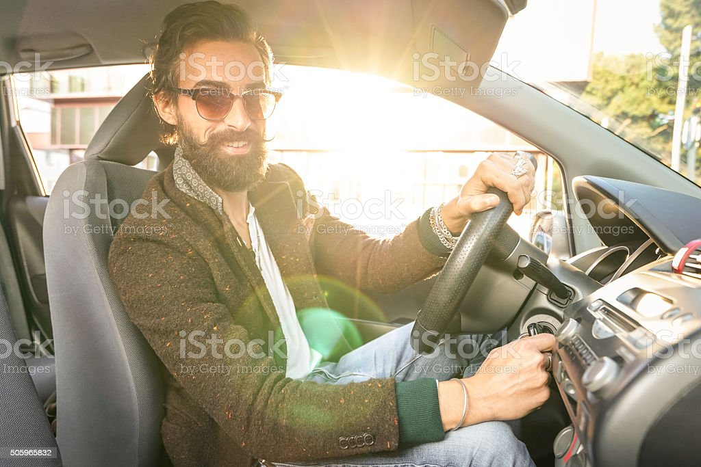 Young hipster fashion model driving car - Handsome confident man stock photo