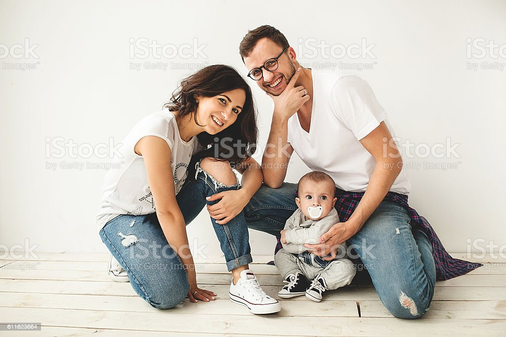 Young hipster father, mother and cute baby boy sitting on rustic...