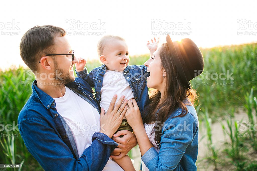 Young hipster father mother holding cute baby in corn field stock photo