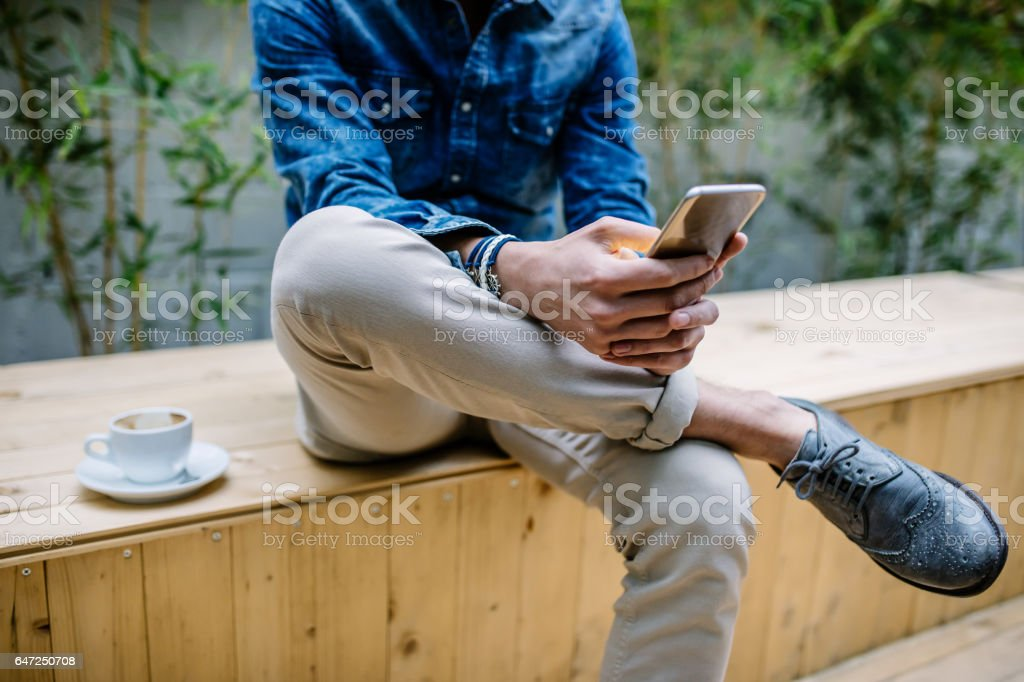 Young hipster guy texting with his mobile phone at the bar and having a cappuccino, close up stock photo