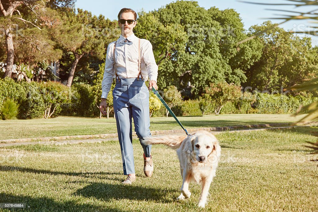 Young Hipster Man and Dog at Park stock photo