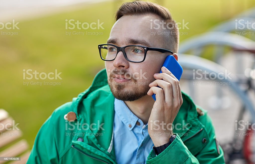 young hipster man calling on smartphone stock photo