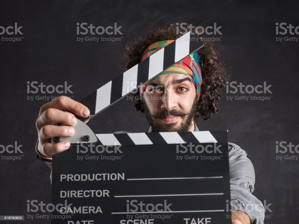 Young hipster man holding a clapperboard stock photo