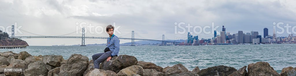 Young hipster man in front of panoramic San Francisco view. stock photo