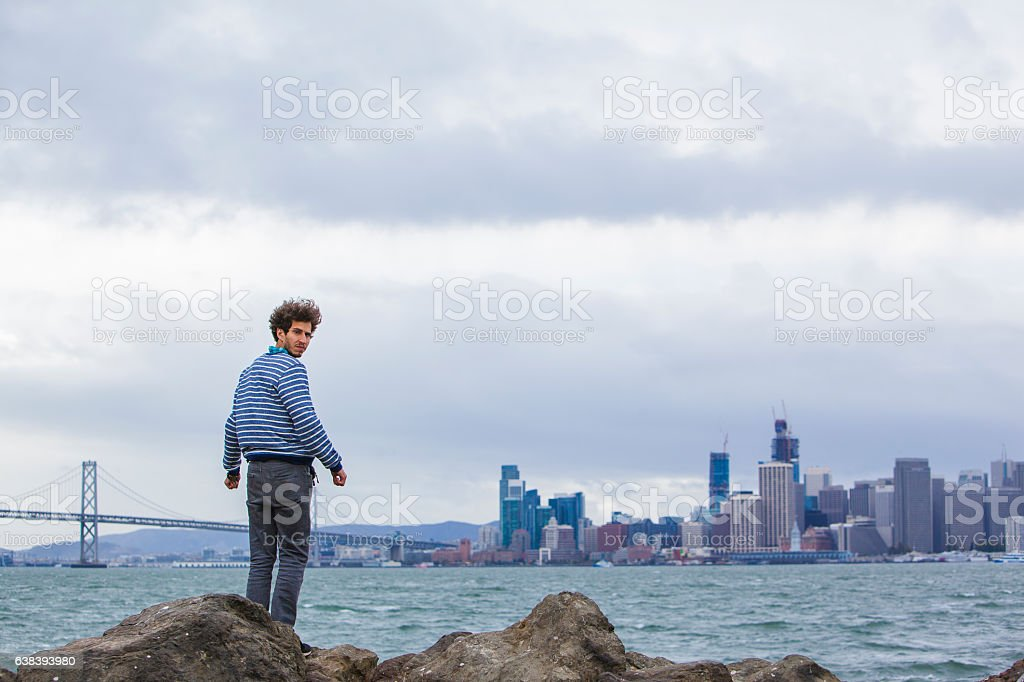 Young hipster man in front of San Francisco view. stock photo