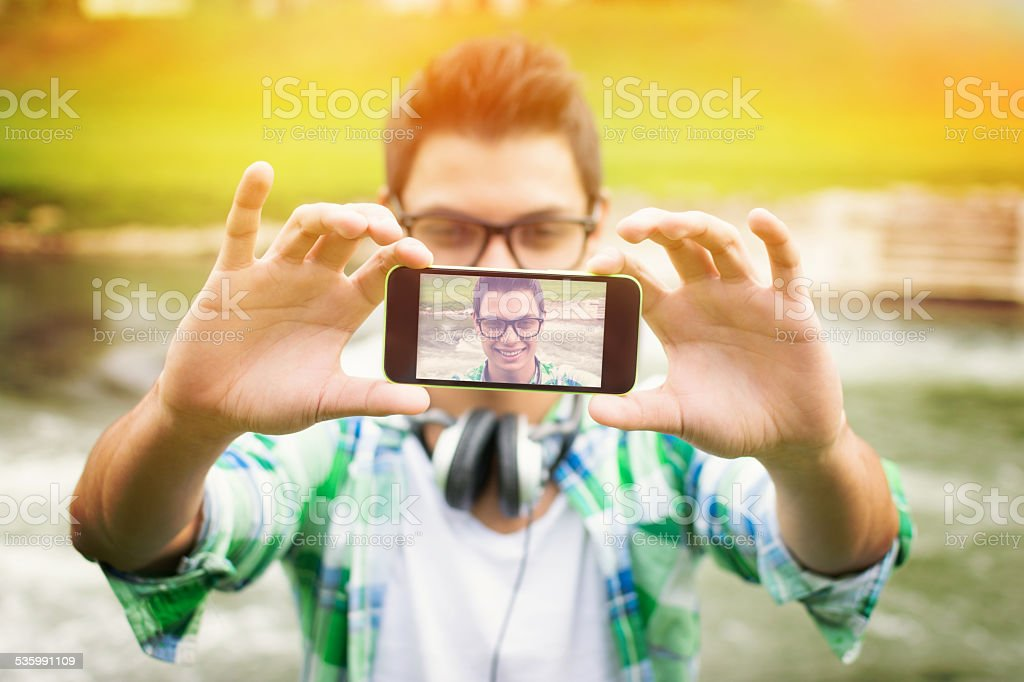 Young hipster man taking a selfie stock photo