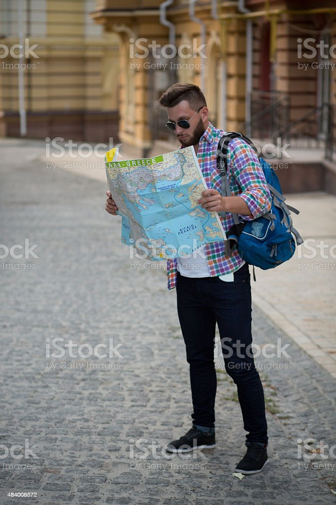 Young hipster man with map stock photo
