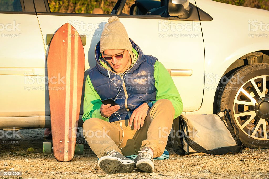 Young hipster man with smartphone sitting next his car stock photo