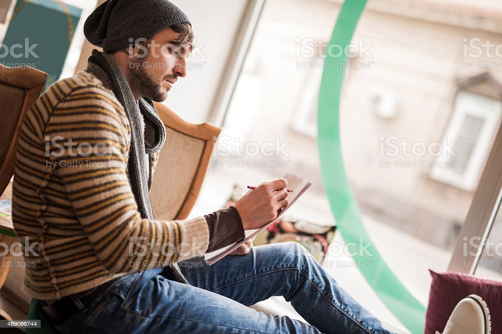Young hipster man writing on a piece of paper. stock photo