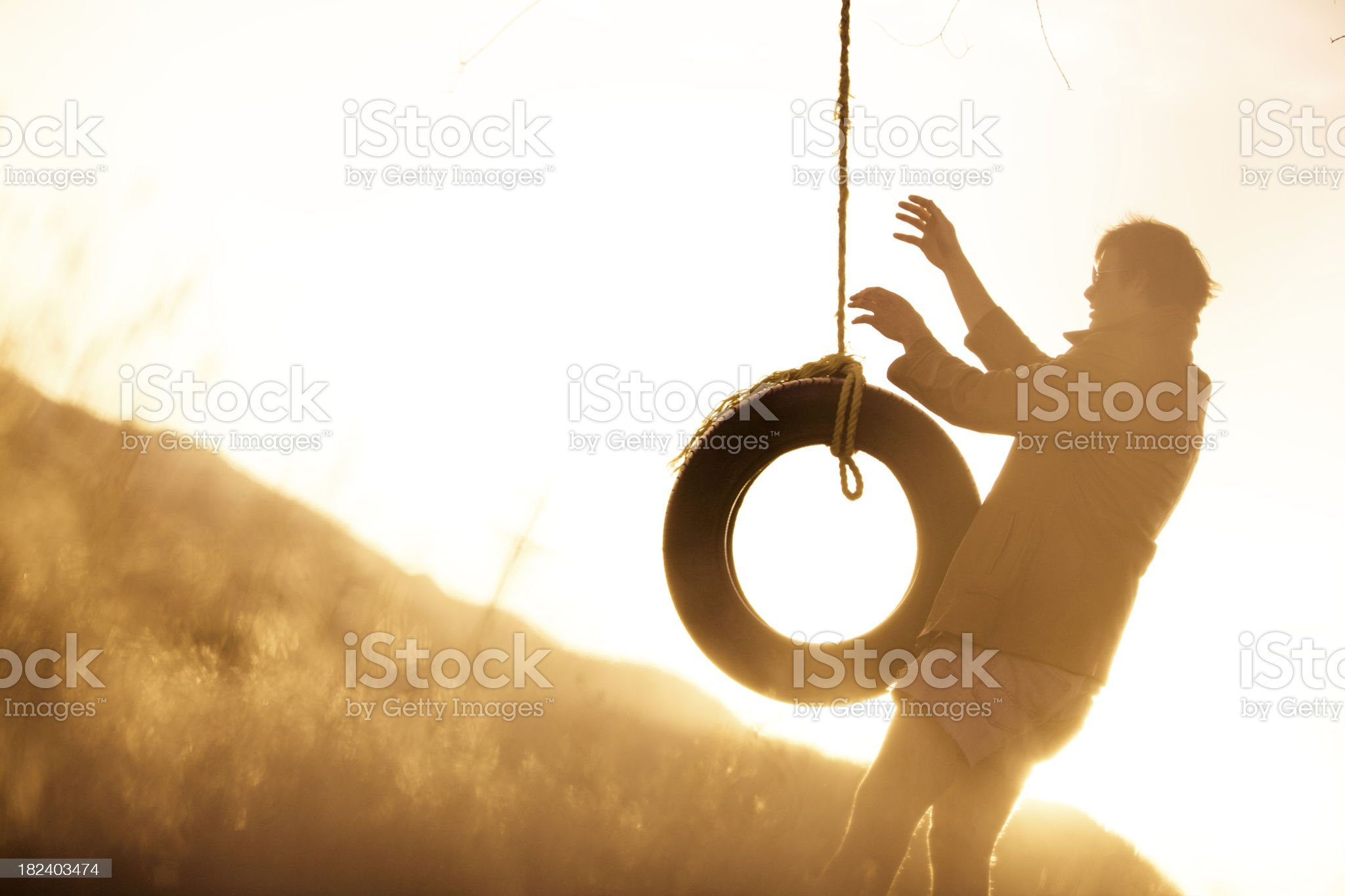 Young hipster swinging on rope swing at sunset royalty-free stock photo