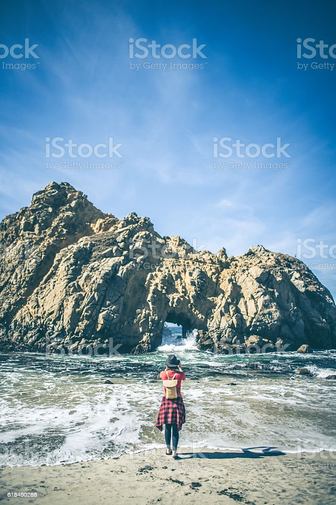 Young hipster taking a picture at the beach stock photo
