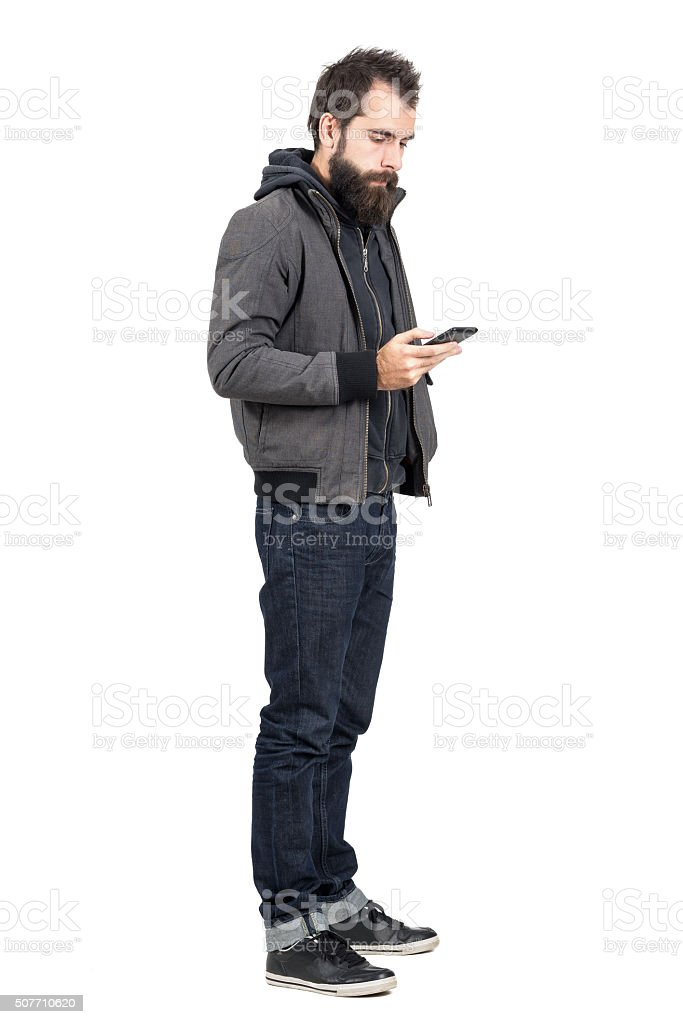 Young hipster wearing jacket typing on mobile phone stock photo