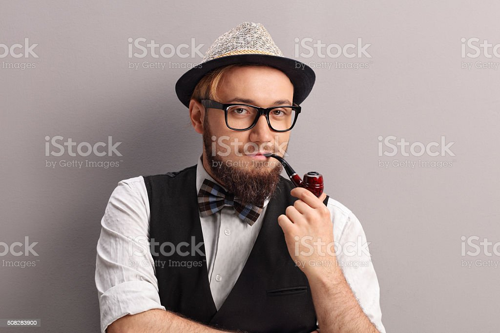 Young hipster with fedora smoking a pipe stock photo