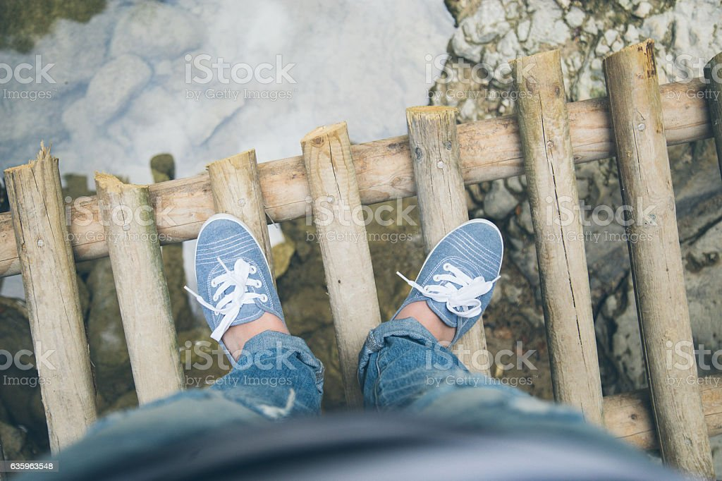 Young hipster woman crossing a bridge stock photo