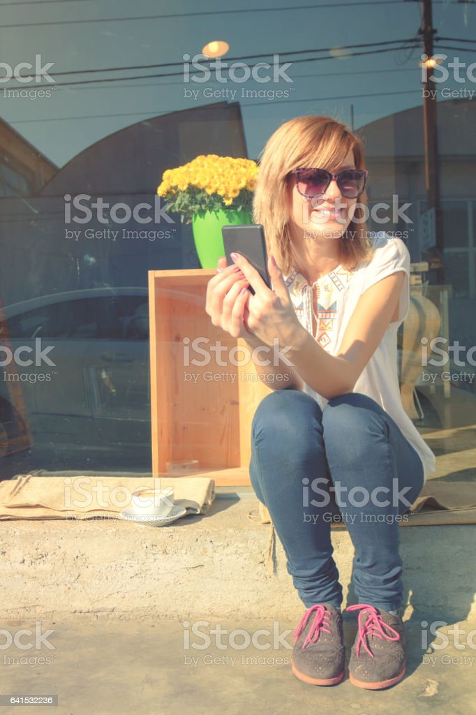 Young hipster woman drinking coffee and using her cellphone outdoors. stock photo