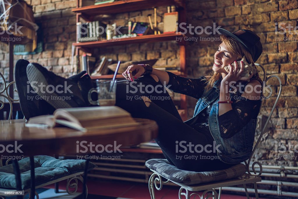 Young hipster woman enjoying in a sound from seashell. stock photo