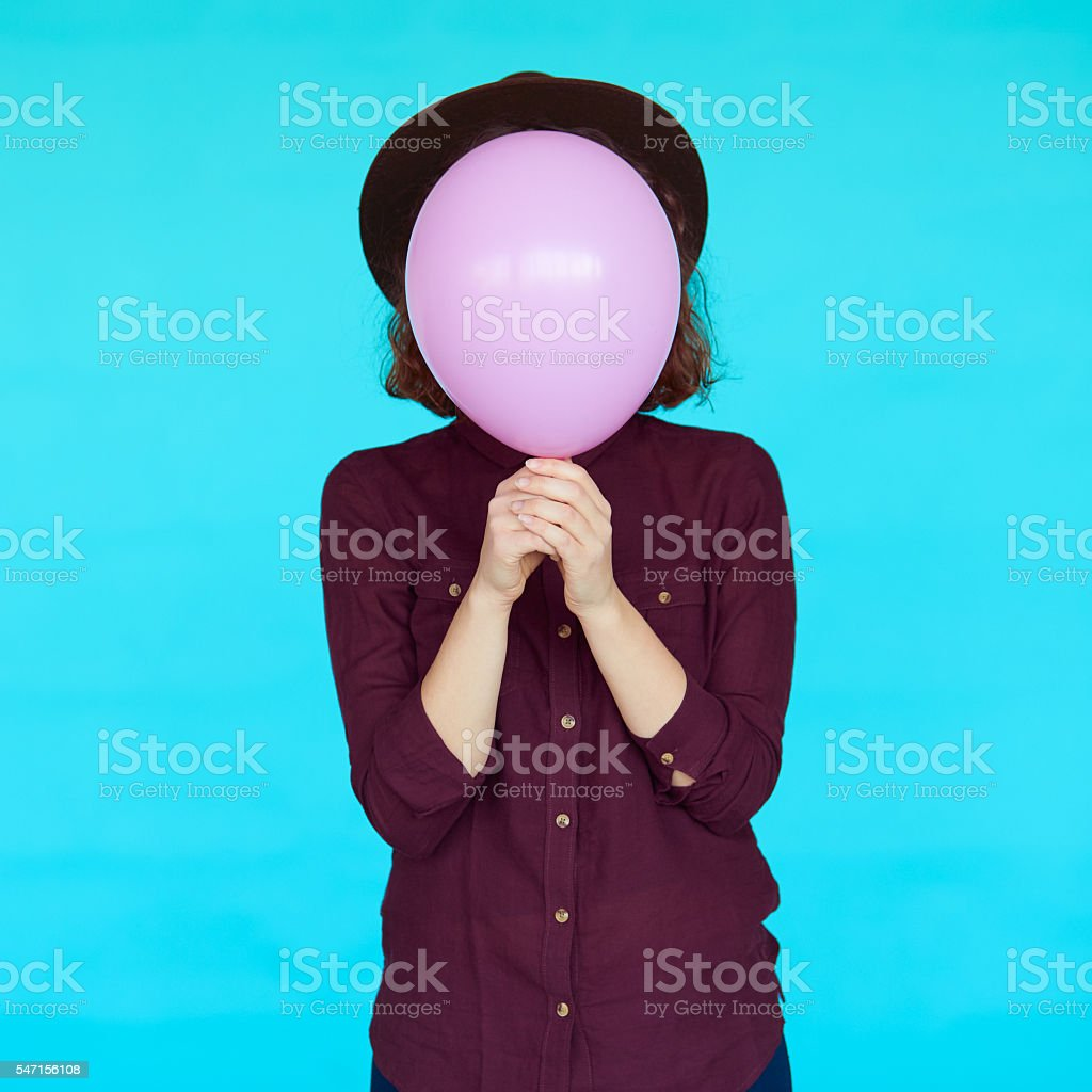 Young hipster woman holding balloon over her face stock photo