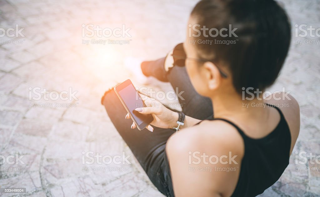 young hipster woman textmessaging on smartphone stock photo