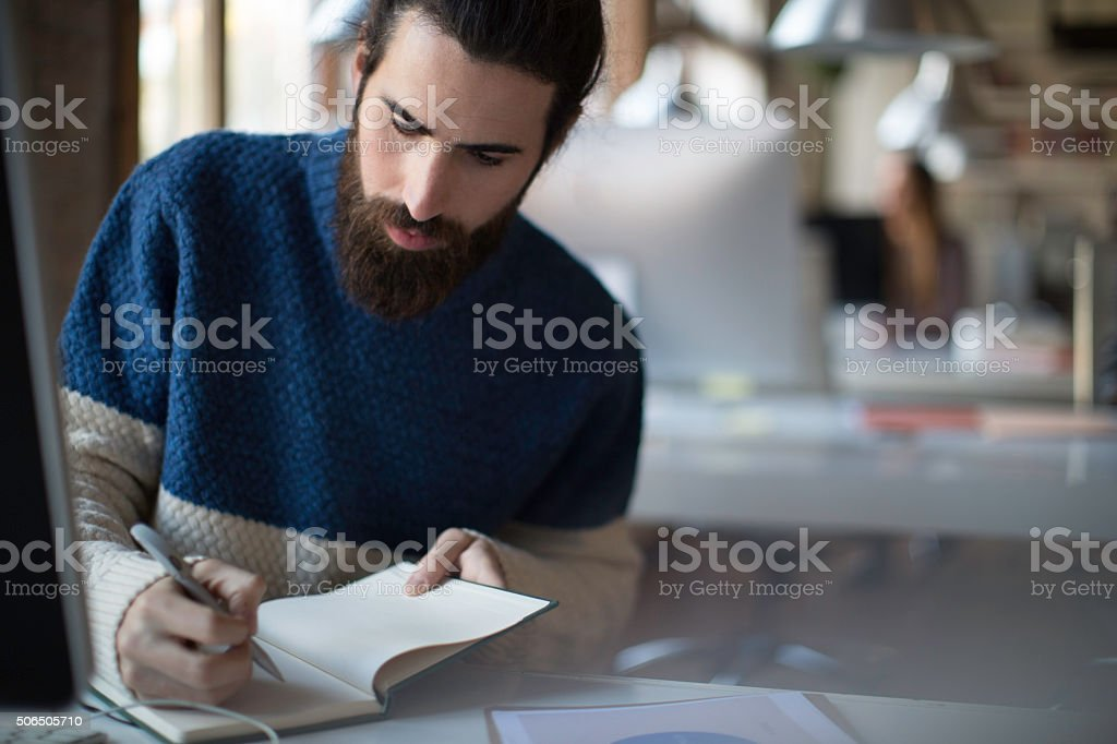 Young hipster working a startup office. stock photo