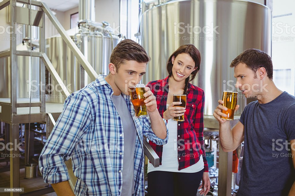 Young hipsters tasting beer together stock photo
