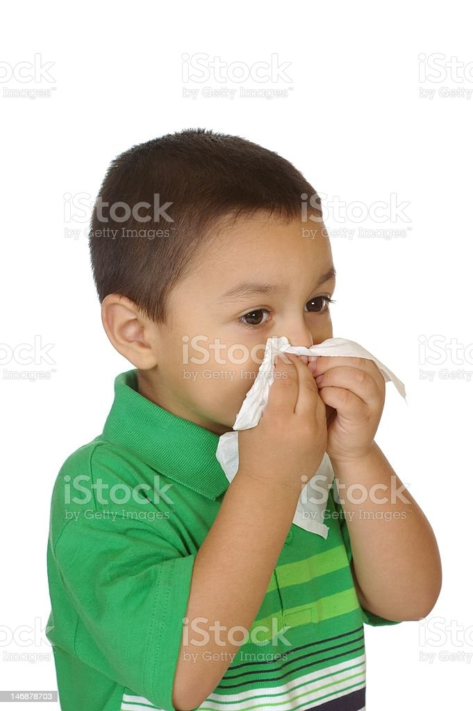 Young Hispanic boy blowing nose with tissue royalty-free stock photo