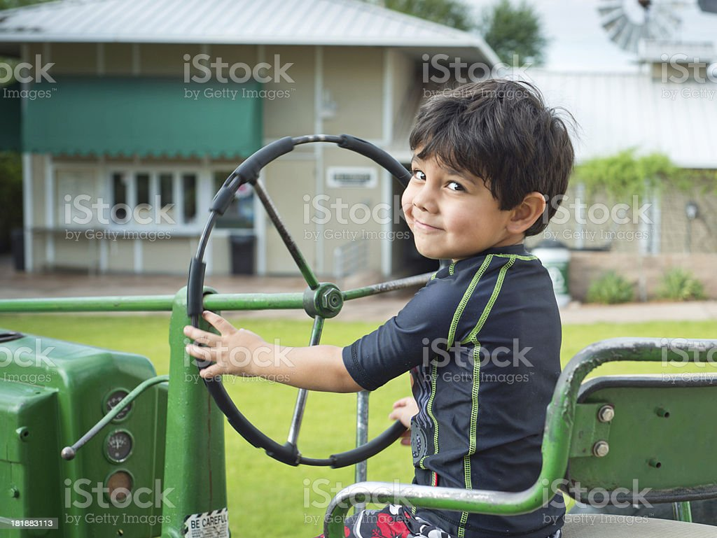 Young Hispanic Boy sitting on old tractor royalty-free stock photo