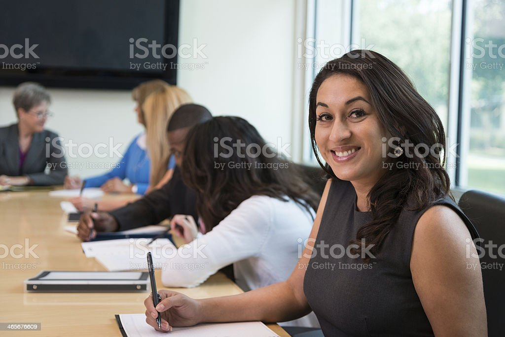 Young Hispanic Businesswoman Smiling During Office Meeting in Board Room stock photo