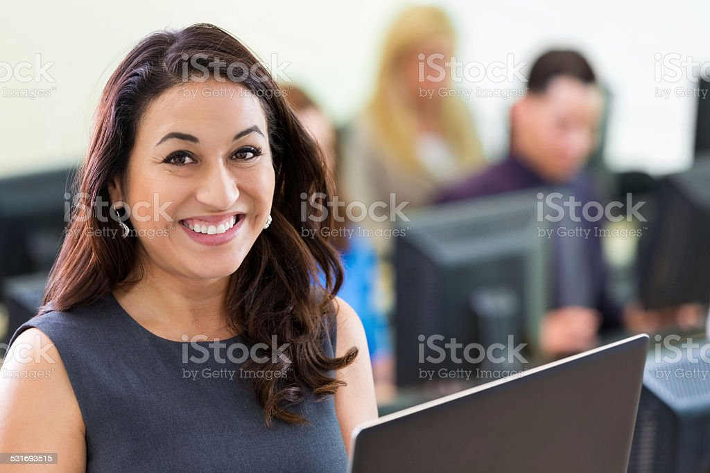 Young Hispanic businesswoman using computer during job training course stock photo