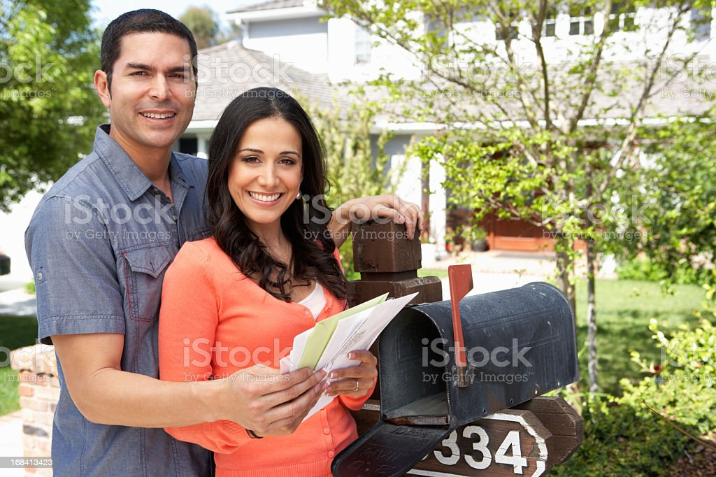 Young Hispanic couple checking the mailbox at their home royalty-free stock photo