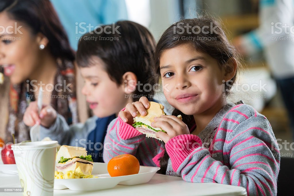 Young Hispanic family eating meal at neighborhood soup kitchen stock photo
