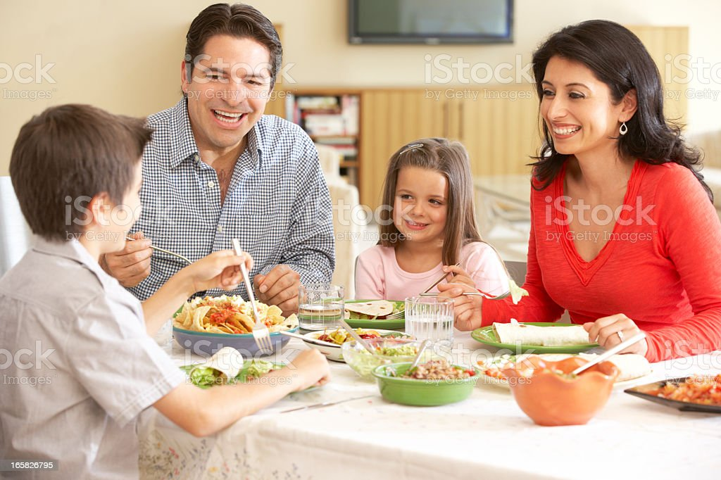 Young Hispanic Family Enjoying Meal At Home stock photo