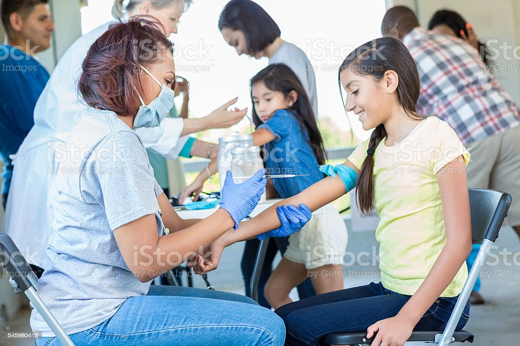 Young hispanic girl about to get a shot stock photo