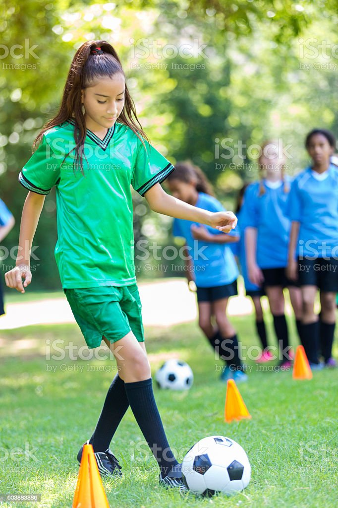 Young Hispanic girl practices soccer drills stock photo