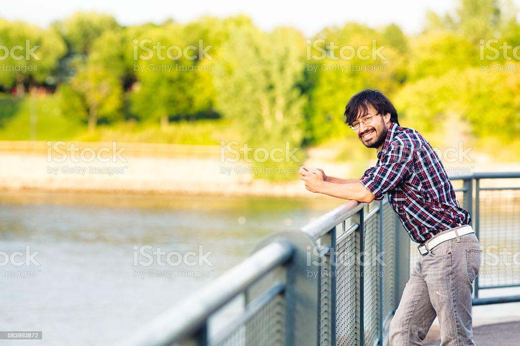 Young Hispanic latin man portrait  relaxing at pier Summer sunset stock photo