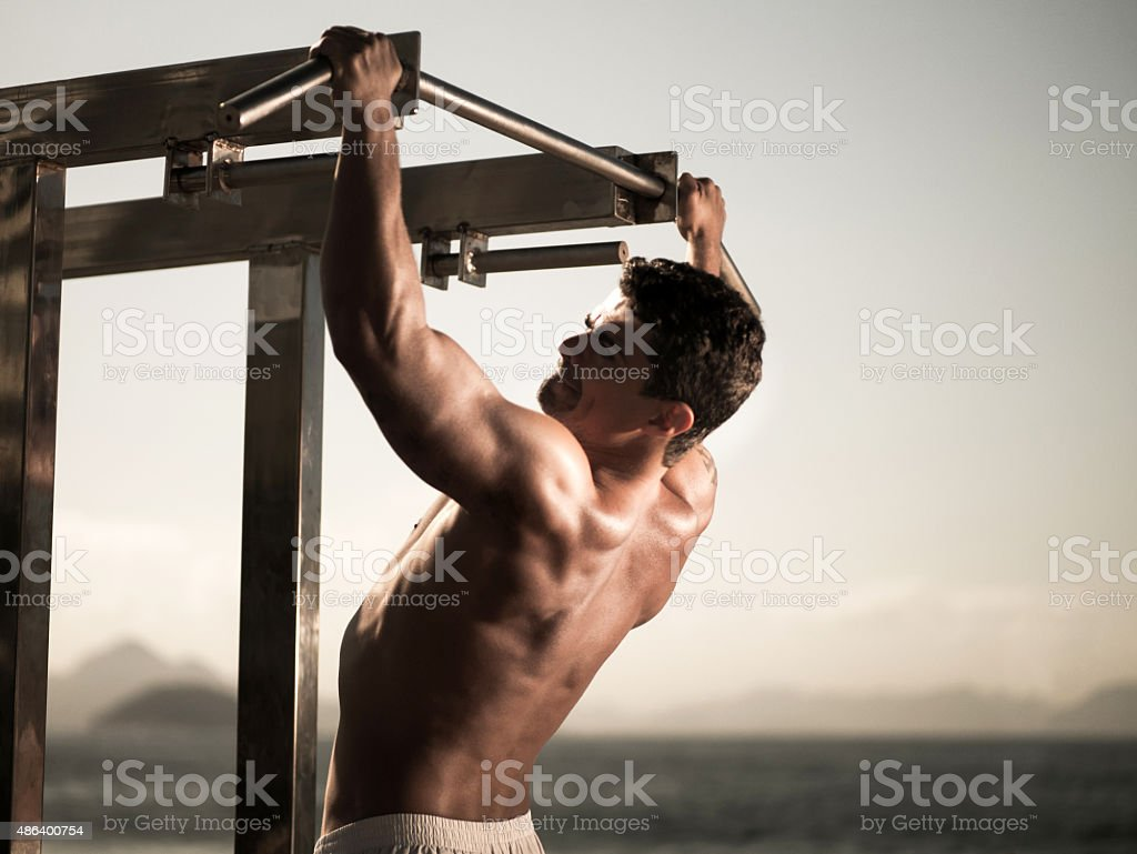 Young Hispanic man exercising arm muscles at the beach. stock photo