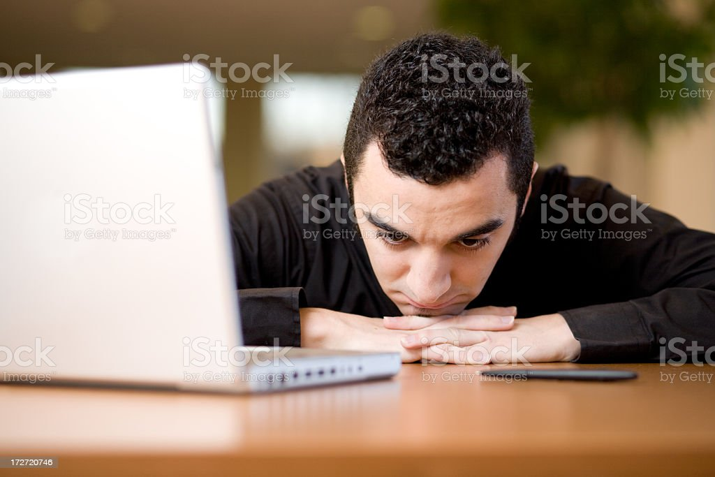 Young hispanic man with his head on a desk stock photo