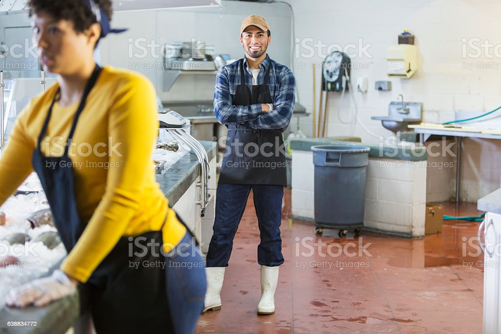 Young Hispanic man working in seafood market stock photo