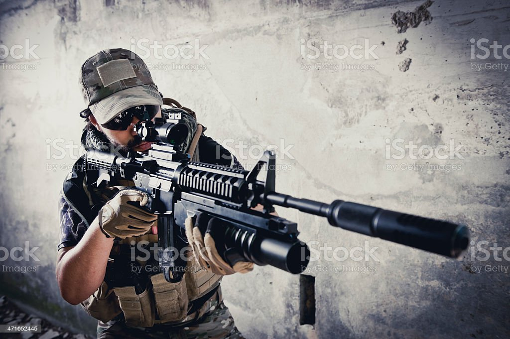 Young Hispanic Modern Army Soldier Aiming with Silenced Assault Rifle stock photo