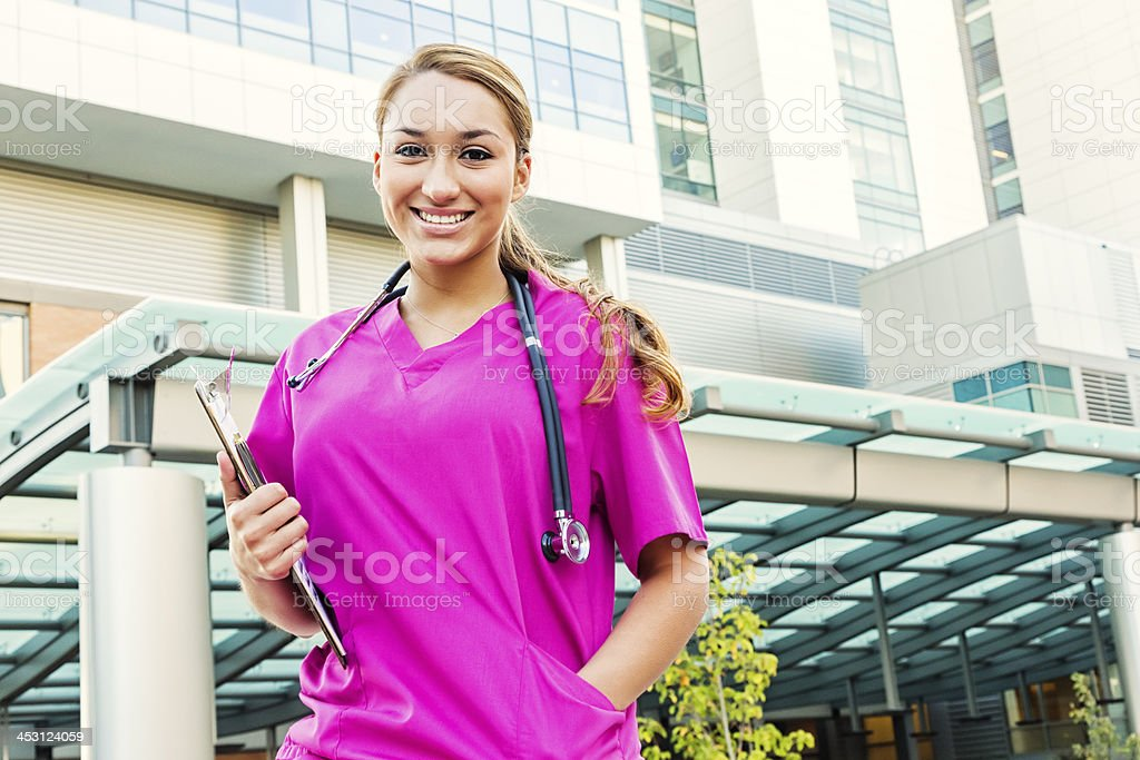Young Hispanic Nurse in Pink Scrubs with Clipboard stock photo