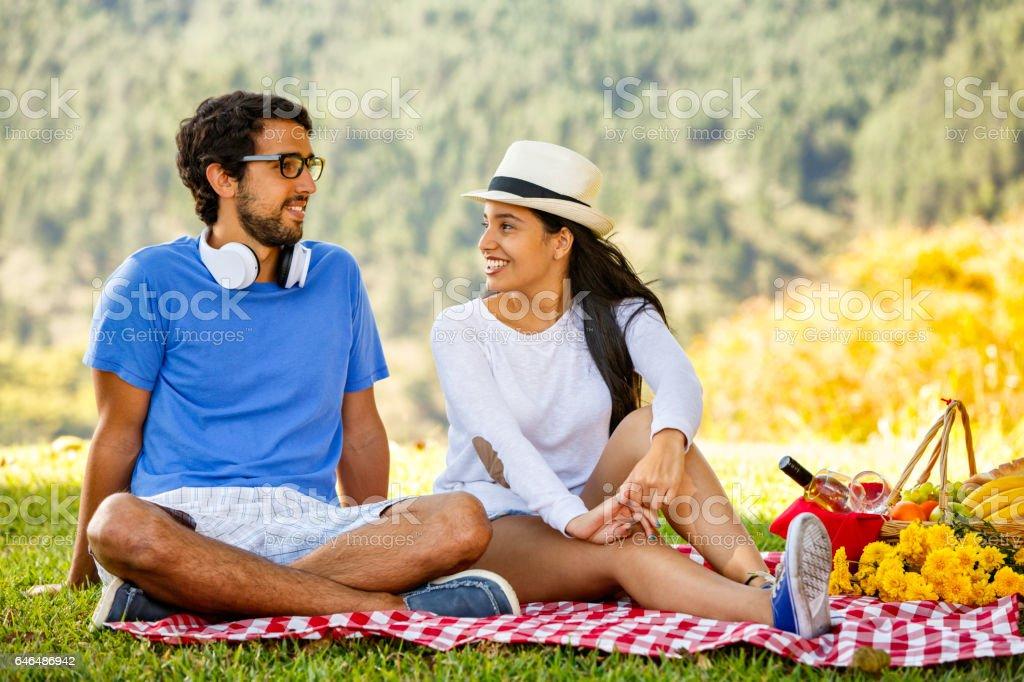 Young hispanic or latin couple enjoying picnic outdoors at park stock photo
