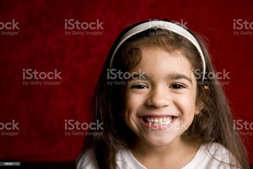 Young Hispanic School Girl with Toothy Smile stock photo