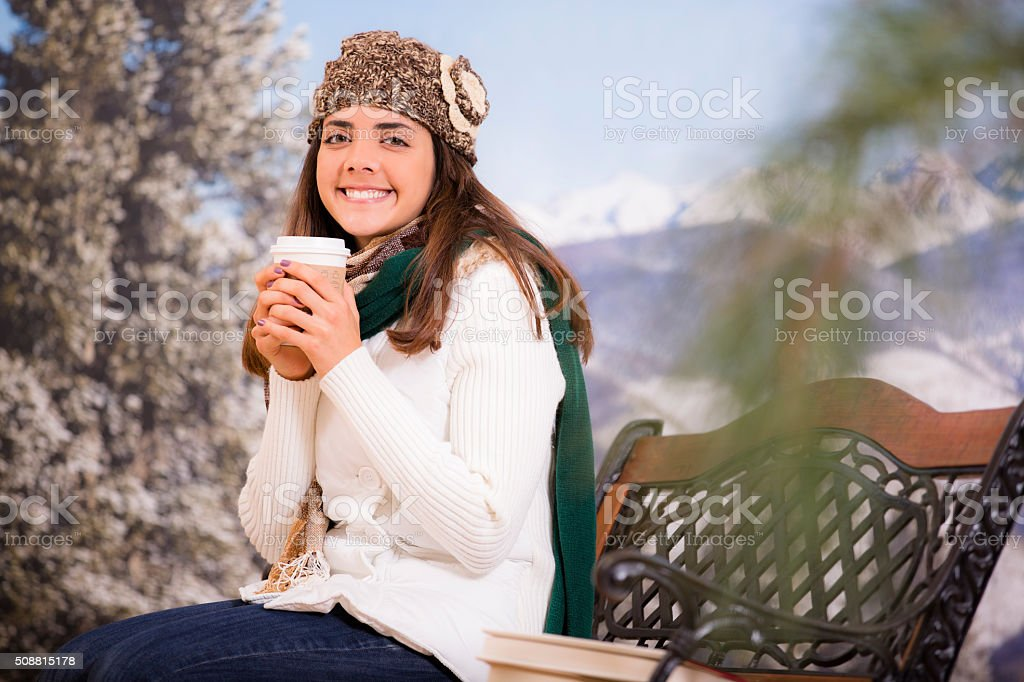 Young hispanic woman holds warm coffee in winter. Mountains, snow. stock photo
