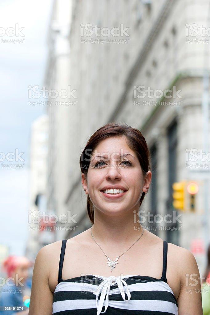 Young Hispanic woman looking upward in downtown city stock photo